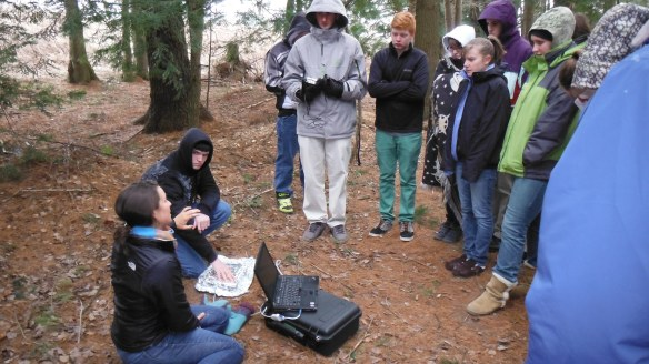 Researcher Elizabeth Webb (seated) explains microbial respiration to BFA-Botany class in the forest understory at BFA