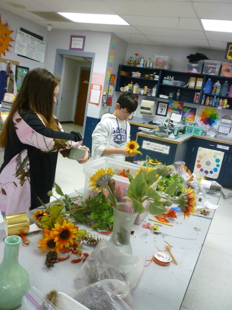 Students work on Thanksgiving centerpieces using dried flowers, pine cones and artificial fall foliage.