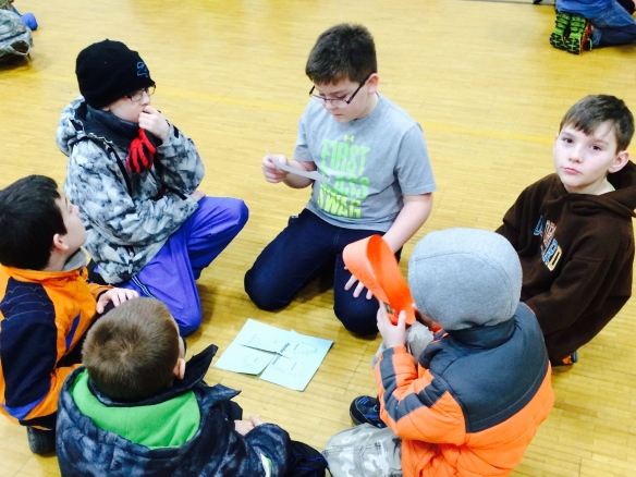 Students work in multi-age groups to assemble a falcon puzzle that helps them review school-wide expectations as part of a whole-school assembly in early January.