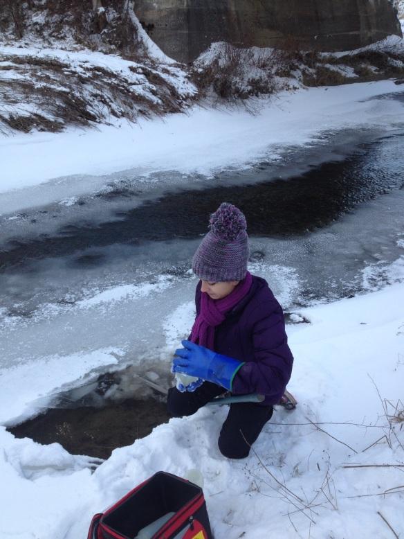 BFA HS student Rebekah Larose collects water samples at Black Creek in East Fairfield, VT
