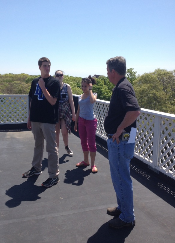 (Facilities Coordinator Fred Palmer explains how the WHRC main building is  efficient to BFA students Dave Legris, Sophie Lee and Rebekah Larose while  standing on its roof.)