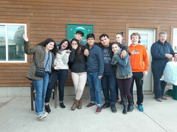 "(Puerto Rican students and BFA students pose outside the milking barn at Bill Rowell's (far right) ""Cow Power"" farm in Sheldon, VT.  Photo credit, Teresa Larose.)"