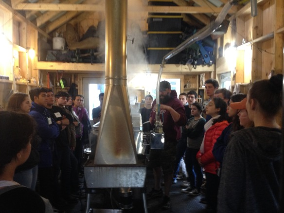 (Puerto Rican exchange students and BFA Botany students visit Jeff Hamel's sugaring operation in Fairfax. (Brooke Hamel, BFA student set-up the visit is in the foreground on the left and Jeff her dad is next to the evaporator.)