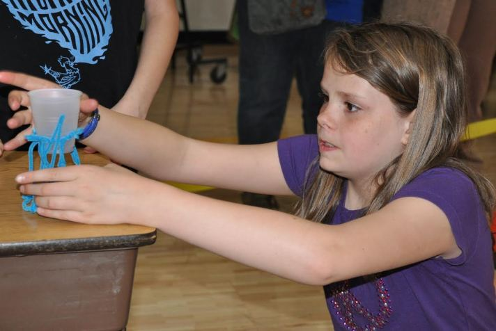 """Fifth grader Elise Towle participates in an engineering """"instant challenge"""" in front of a live audience as part of STEM Night."""