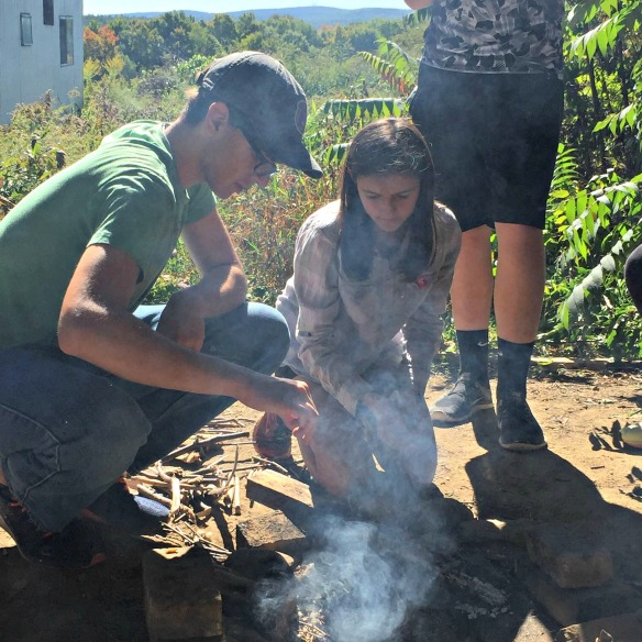 Alex H and Rachel P work to build a fire to cook their lunch.