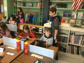 7th and 8th grade students assist 4th graders with the online voting system.