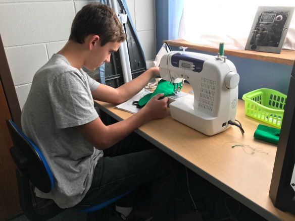 Student using sewing machine.