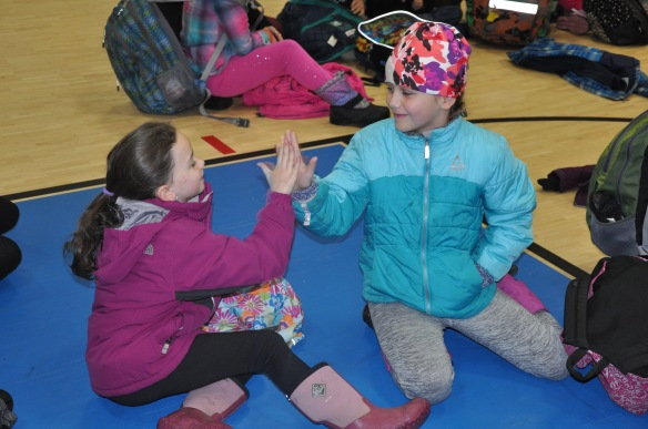 Two Fletcher students greet each other with a high five during a whole-school celebration. The celebrations serve to review and practice social skills, celebrate success with behavior and build community.