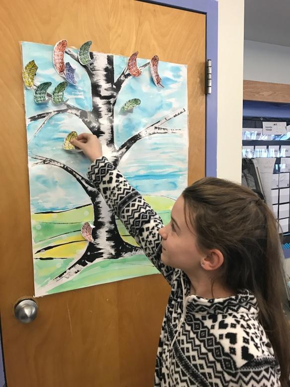 A Fletcher student puts a token on her classroom PBIS chart.