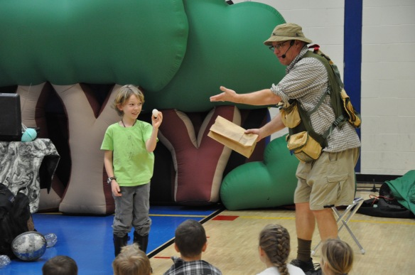"Fletcher Elementary School third grader, Serein, assists paleontologist and comedian Bob ""Dinoman"" Lisaius by holding a ""dinosaur egg"" during a whole-school presentation on Monday."