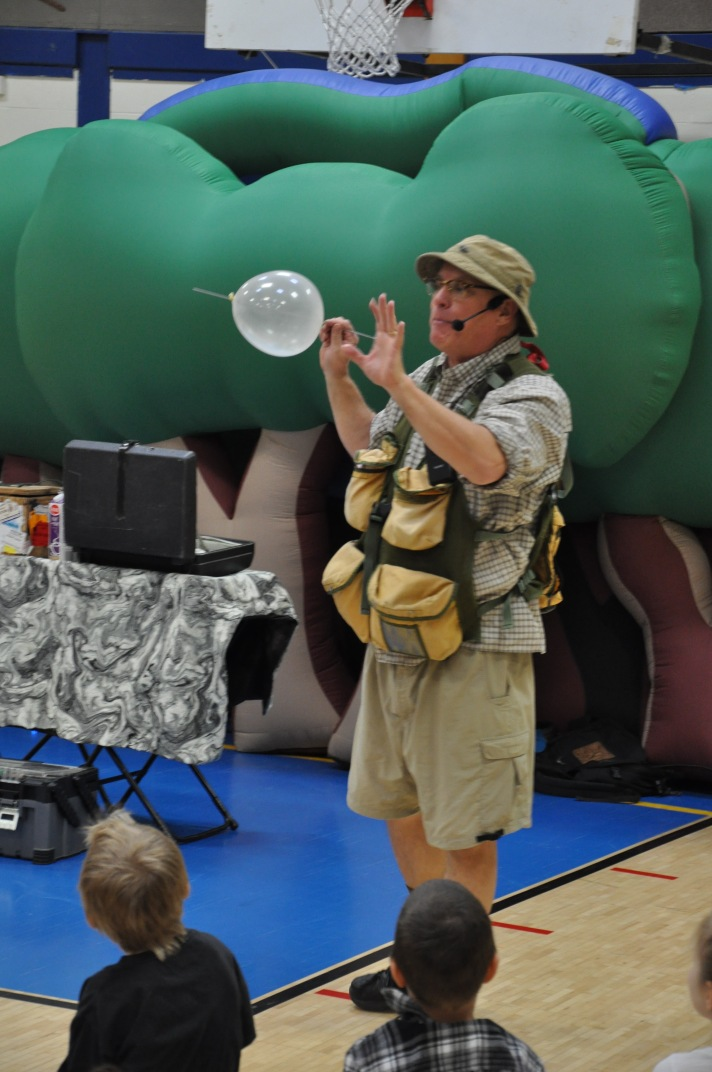 Comedian and paleontologist Bob Lisaius uses a balloon and skewer to demonstrate how oxygen traveled through dinosaur eggs in order to reach the developing young.
