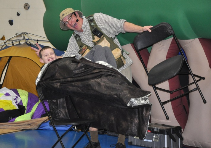 "Fletcher Elementary School fifth grader, Bryant, and Bob ""Dinoman"" Lisaius, demonstrate how a Tyrannosaurus Rex balanced on two feet."