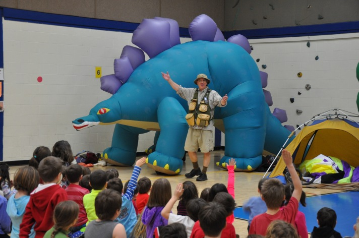 """Warren, VT-based paleontologist and comedian Bob """"Dinoman"""" Lisaius stands in front of one of three inflatable dinosaurs used during a presentation at the Fletcher Elementary School on Monday."""