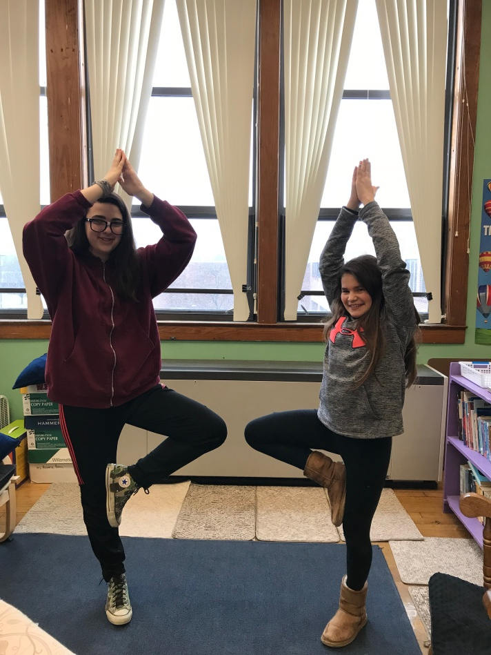 students in a yoga pose during sensory break