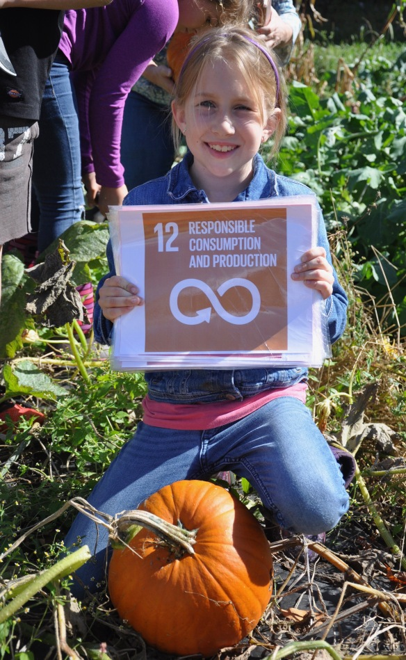 "A Fletcher Elementary students poses with a pumpkin as she offers a reminder of UN Global Goal 12 ""Responsible Consumption and Production"""
