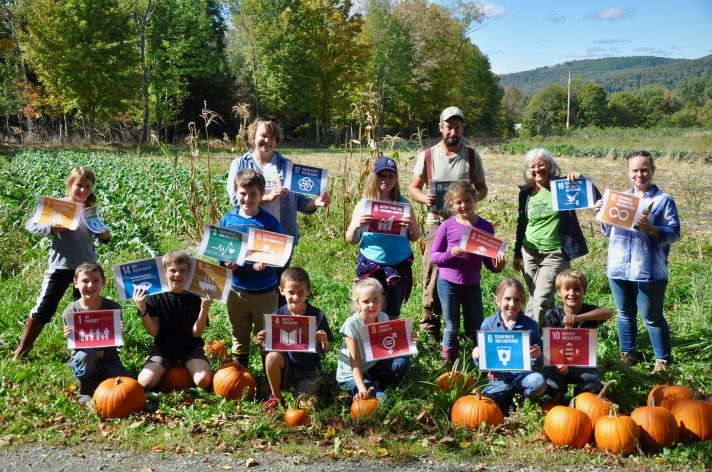 Fletcher Elementary students pose with the UN Global Goals for Sustainability at the West Farm in Jeffersonville, VT