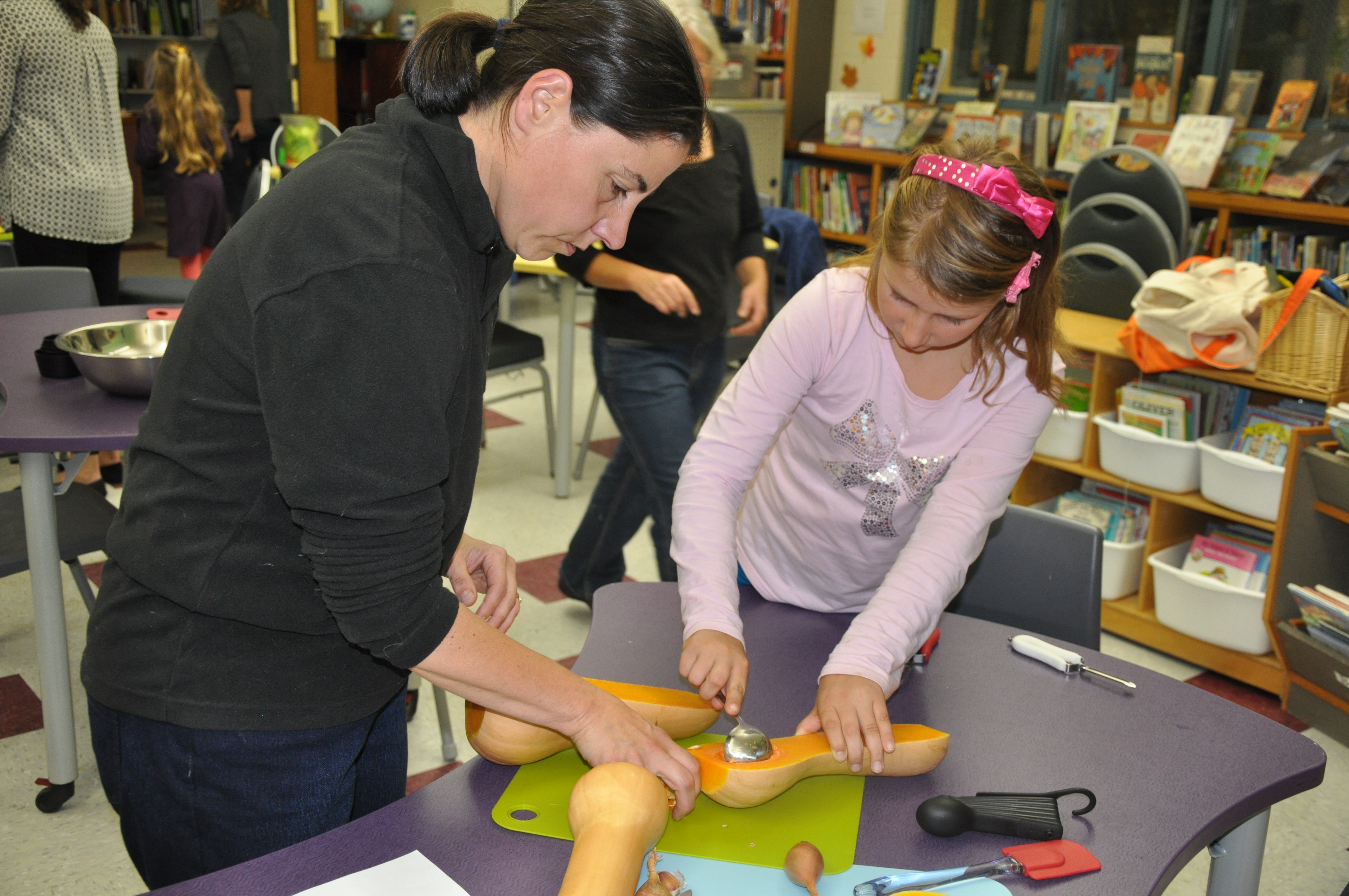 A student harvests squash with her parent as part of a cooking class at Fletcher Elementary School