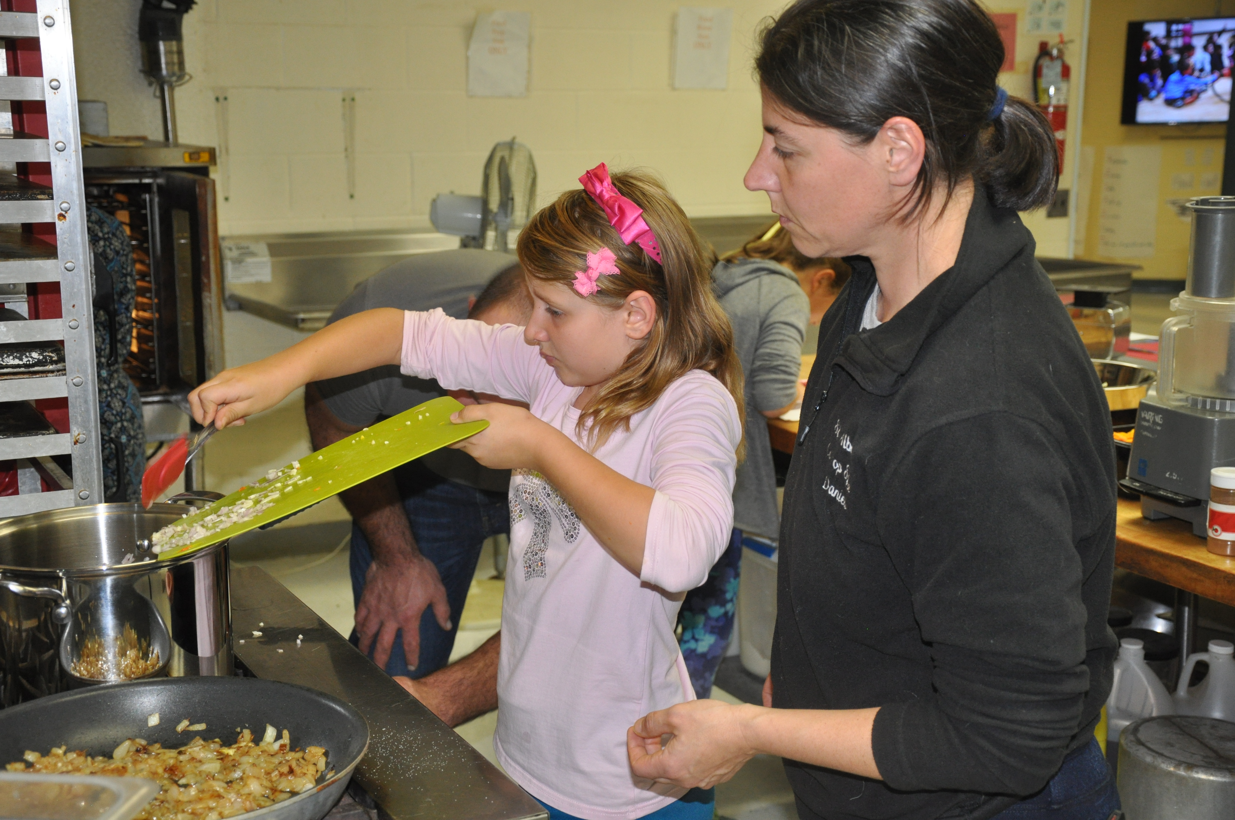A student cooks in the kitchen at Fletcher Elementary School
