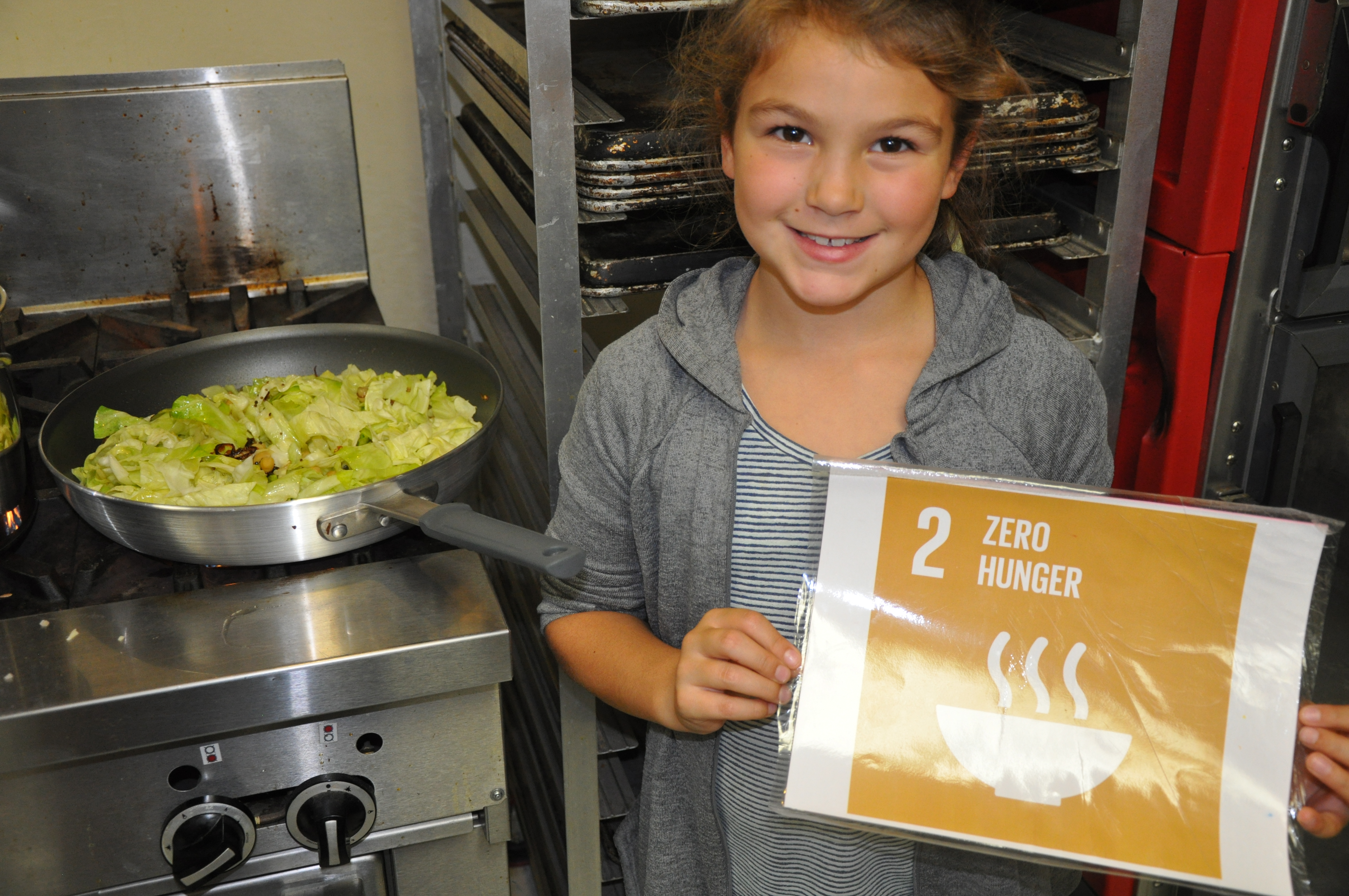 A Fletcher Elementary student poses with her harvested cabbage and UN SDG #2 Zero Hunger