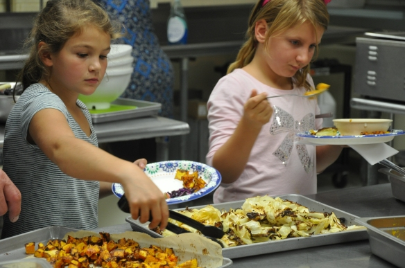 Students serve their harvested vegetables prepared in the Fletcher Elementary School kitchen