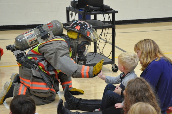 Cambridge Firefighter Elizabeth Rowe high-fives Elementary Preschooler during fire safety exercise