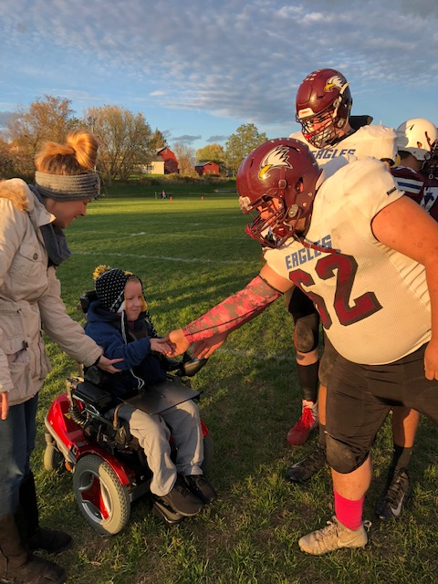 Fairfax football players greet BFA Fairfax first grader Asher Lawrence